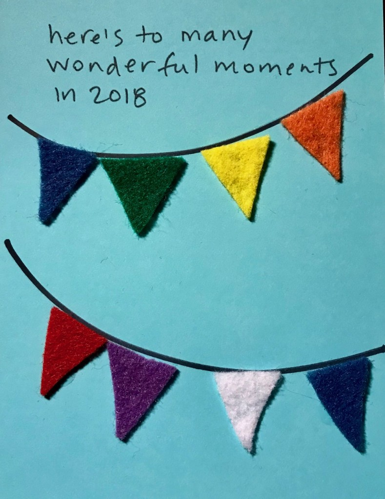 "[image of a light blue card with black lettering reading ""here's to many wonderful moments in 2018"" above two banners of triangular pennants cut out of colored felt]"